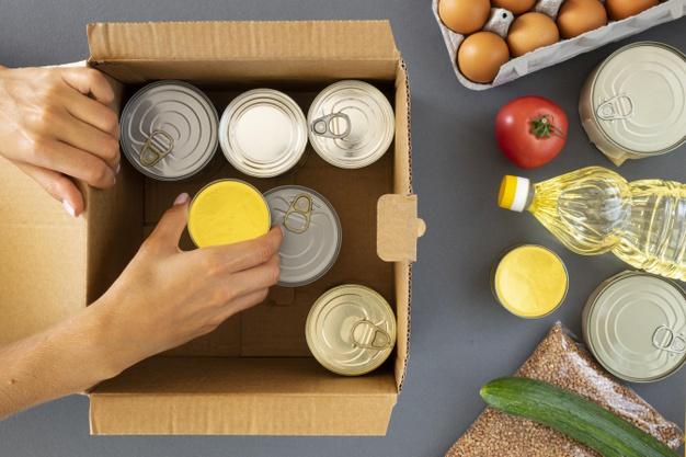 vista-superior-mano-preparando-donaciones-alimentos-caja_23-2148733831